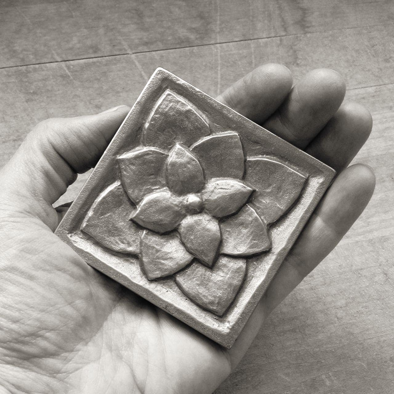 Foundry Art Lotus 3-inch metal accent inset tile in hand